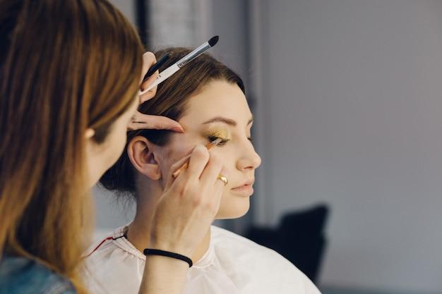 Make-upkunstenaar die oogschaduw op de ogen van het model toepast