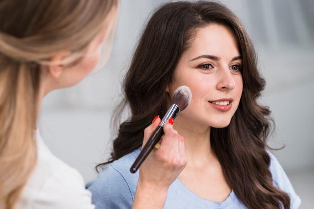 Make-upkunstenaar die van toepassing zijn bloost met professionele borstel