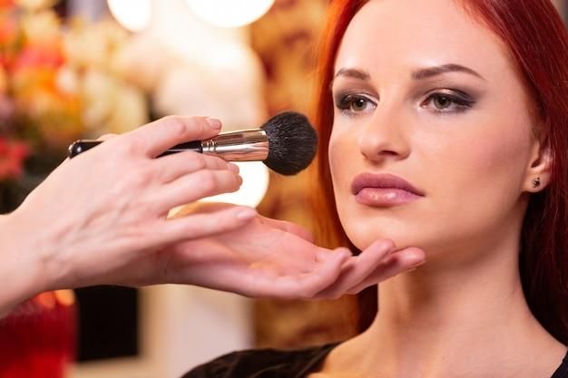 Make-upkunstenaar die vloeibare tonale stichting op het gezicht van de vrouw toepast