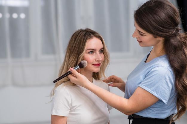 Make-upkunstenaar die vrouw voorbereiden