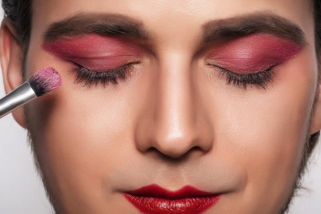 Make-uplook voor heren. close-up portret van een jonge, bebaarde man met een make-upborstel