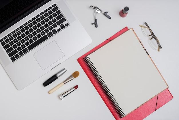 Make-upobjecten met mappen voor laptop en kantoor; lenzenvloeistof op wit bureau