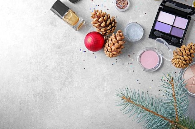 Make-upproducten en kerstversieringen op gekleurde achtergrond