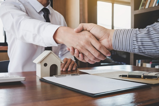 Makelaar agent en klant handen schudden na ondertekening van contractdocumenten