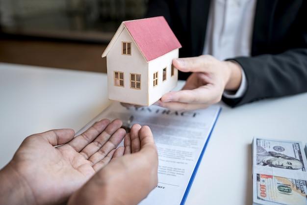 Makelaar die een woningkrediet voorstelt en een huismodel aan de klant geeft