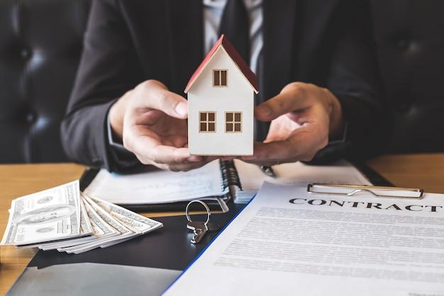 Makelaar die huismodel naar cliënt verzendt na het ondertekenen van overeenkomstcontract onroerende goederen met vorm