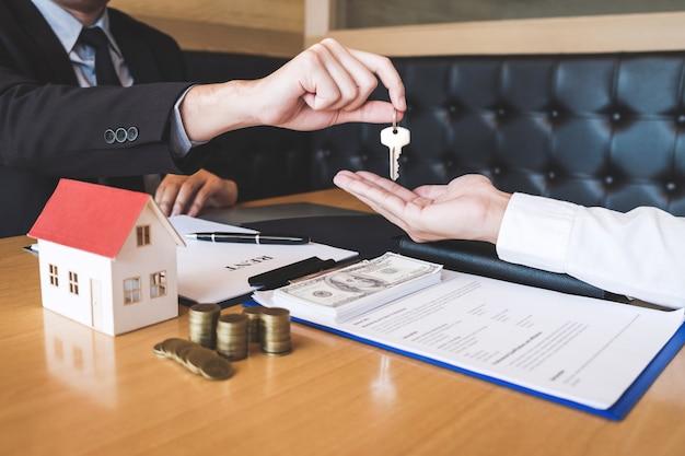 Makelaar die huissleutels aan cliënt geeft na ondertekening overeenkomst contract onroerend goed met goedgekeurd hypotheekaanvraagformulier, betreffende hypothecaire leningaanbieding en huisverzekering