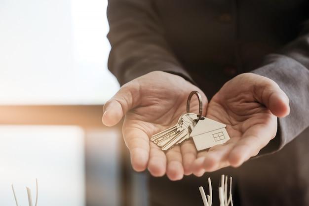 Makelaar die huissleutels overhandigt met goedgekeurd hypotheekaanvraagformulier en handdruk aanbiedt