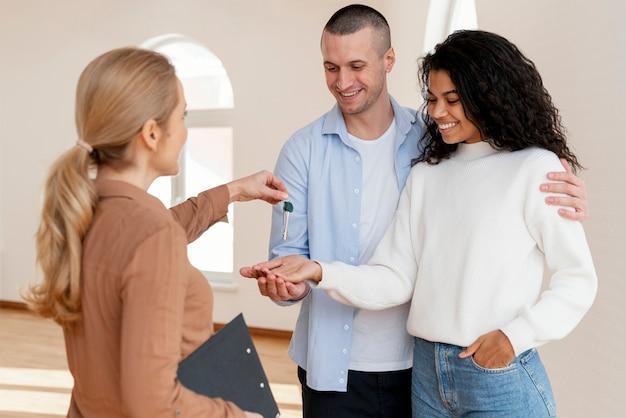 Makelaar die smileypaar de sleutels voor hun nieuwe huis overhandigt