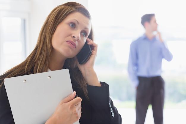 Makelaar die teleurgesteld op de telefoon kijkt