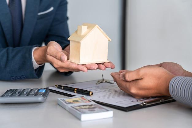 Makelaar die woningkrediet voorstelt en sleutels geeft aan de klant