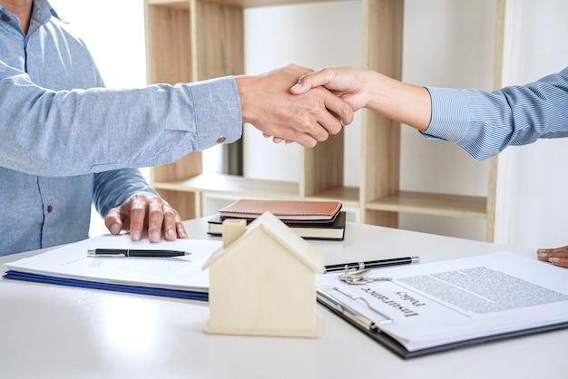 Makelaar en klanten schudden samen de hand om het voltooide contract na ondertekening te vieren