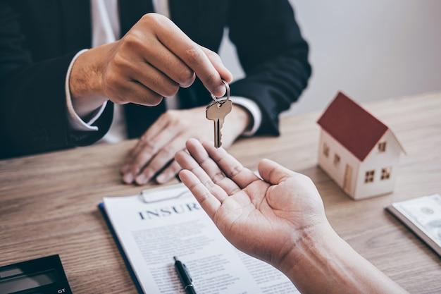 Makelaar geeft huissleutels aan klant na ondertekening overeenkomst contract onroerend goed met goedgekeurd hypotheekaanvraagformulier, met betrekking tot hypothecaire leningaanbieding voor en huisverzekering.