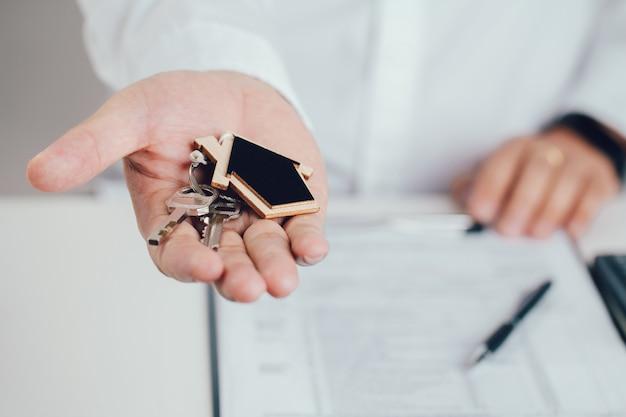Makelaar hand met huissleutels met huisvormige sleutelhanger. hypotheek begrip. onroerend goed, verhuizen of onroerend goed huren.