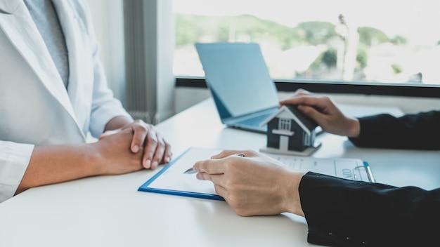 Makelaar hand met pen en uitleg over het zakelijke contract, huur, koop, hypotheek, lening of woningverzekering.