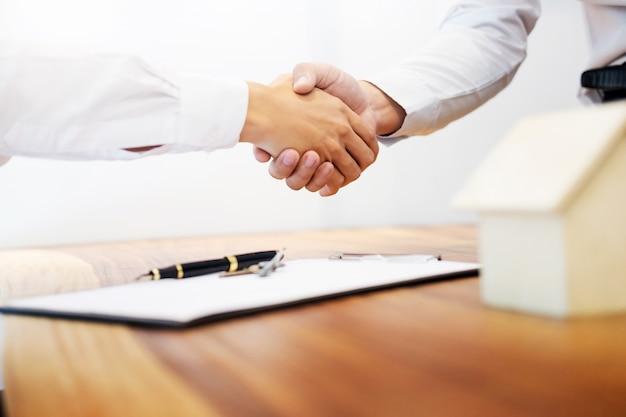 Makelaar handschudden met klant na contract ondertekening als succesvolle overeenkomst in makelaarskantoor kantoor. concept woningbouw en verzekering