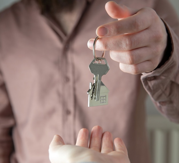 Makelaar huissleutels geven aan klant voor nieuw huis, contract onroerend goed voor hypotheek goedgekeurd, focus op sleutels, zakelijk, financieel, estate concept dicht bij