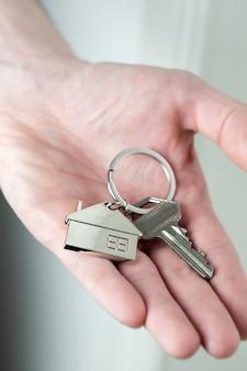Makelaar huissleutels geven aan klant voor nieuw huis, contract onroerend goed voor hypotheek goedgekeurd, focus op sleutels, zakelijk, financieel, estate concept