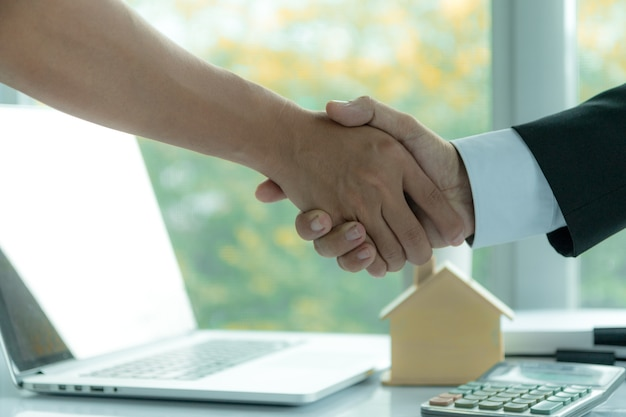 Makelaar in bureau die handen met klanten schudden na het ondertekenen van een contract van de huisaankoop