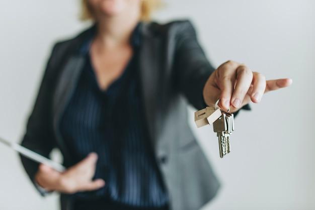 Makelaar in onroerend goed die de sleutels overhandigen