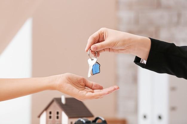 Makelaar in onroerend goed die een sleutel van nieuw huis geven aan cliënt in bureau