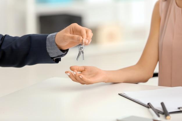 Makelaar in onroerend goed die sleutel van nieuw huis geeft aan jonge vrouw op kantoor