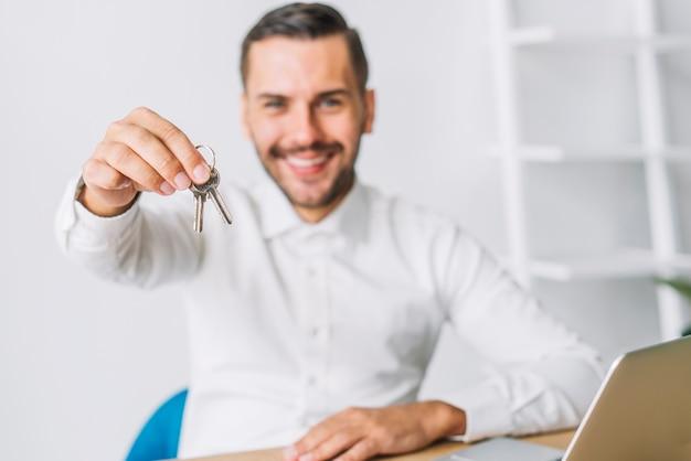 Makelaar in onroerend goed die sleutels houdt