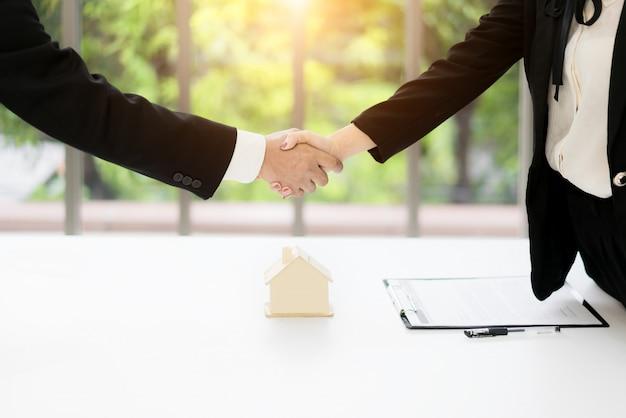 Makelaar in onroerend goed en klant handen schudden na ondertekening van een contract