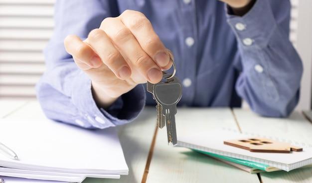 Makelaar in onroerend goed geeft de sleutels aan de koper van het huis en ondertekent het contract op kantoor.