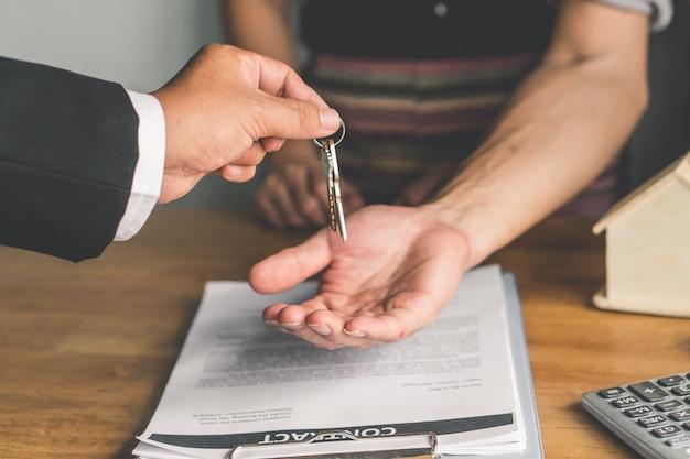 Makelaar in onroerend goed geeft een sleutel van appartement aan nieuwe eigenaar na ondertekende huurovereenkomst.