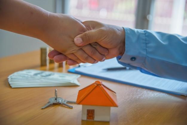 Makelaar in onroerend goed handen schudden met klant na ondertekening van het contract