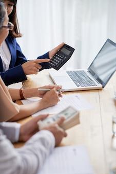 Makelaar in onroerend goed helpt senior koppel om hypotheekbetaling en aanbetaling te berekenen