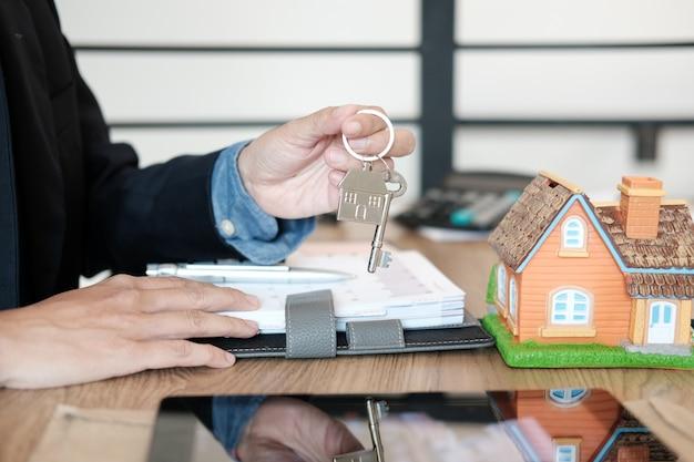 Makelaar in onroerend goed met huismodel en huissleutel, huurend onroerend goed kopen