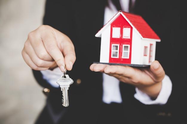 Makelaar in onroerend goed met huismodel en sleutels