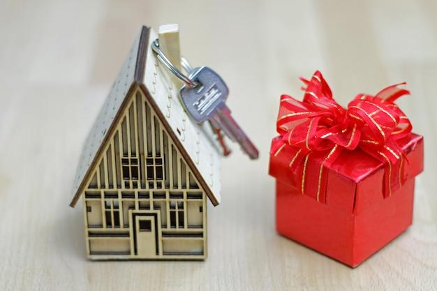 Makelaar in onroerend goed met huismodel, geschenkdoos en sleutels