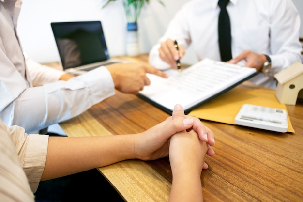 Makelaar in onroerend goed met klant die contracthandtekening maakt en waardering analyseert