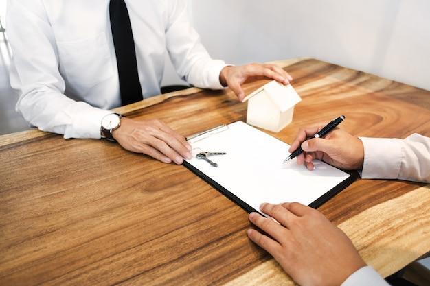 Makelaar in onroerend goed met klant die contracthandtekening maakt, koopt / huurt een huis