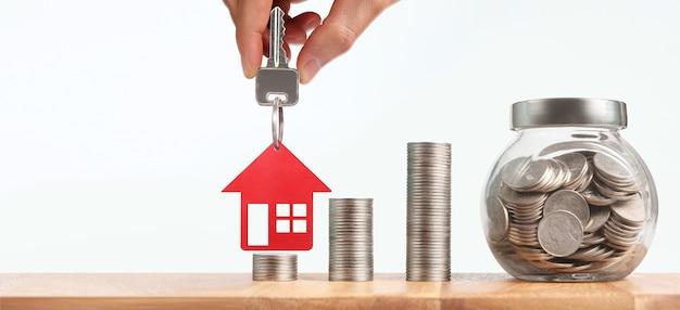 Makelaar in onroerend goed overhandigen een huissleutels in de hand, en munten