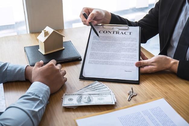 Makelaar in onroerend goed presenteert woningkrediet en geeft huis, sleutels aan klant na ondertekening van contract