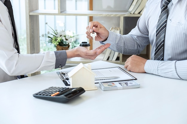 Makelaar in onroerend goed presenteert woningkrediet en stuurt sleutels naar klant na ondertekening van het contract