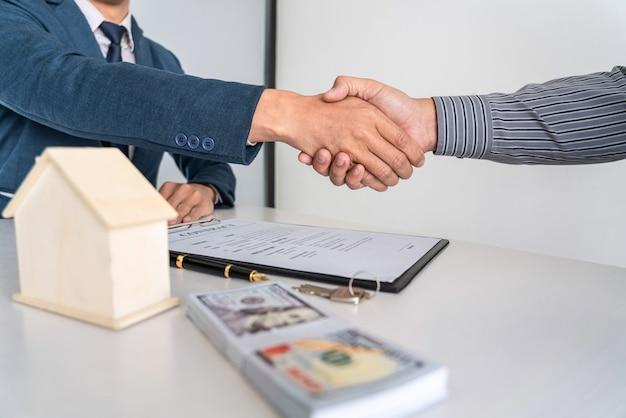 Makelaar in onroerend goed schudden handen na een goede deal en geven huis, sleutels aan de klant na het ondertekenen van een contract om een huis te kopen met een goedgekeurd aanvraagformulier voor onroerend goed