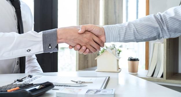 Makelaar in onroerend goed schudt handen na goede deal en geeft huis, sleutels aan klant na ondertekening contract