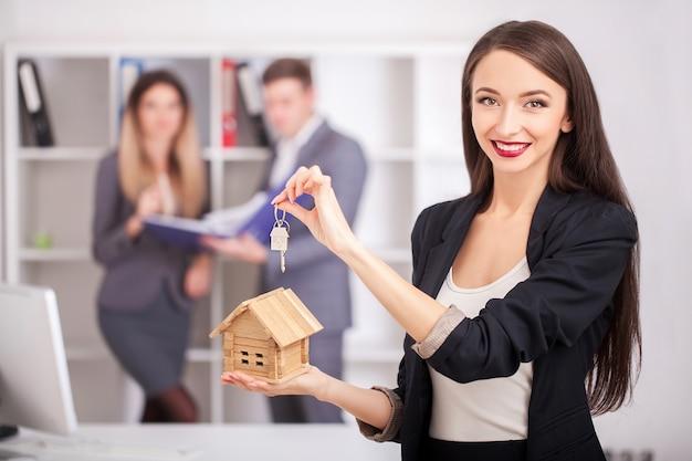 Makelaar in onroerend goedportret met familie die nieuw huis krijgen.