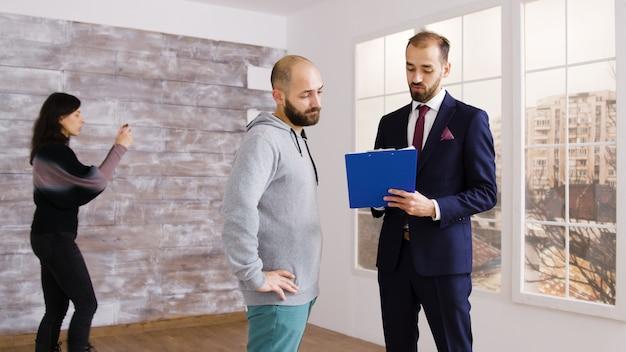 Makelaar in pak beschrijft appartement aan klant in leeg pand terwijl vrouw foto's maakt op de achtergrond.