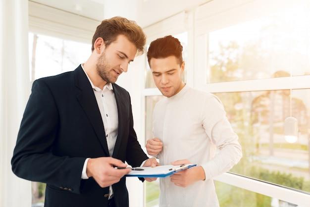 Makelaar is in gesprek met de klant voor het kopen van onroerend goed.