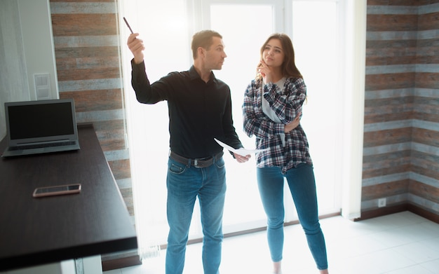 Makelaar, makelaar of verhuurder toont een appartement aan een jonge vrouw. ze gaat met hem een huurovereenkomst tekenen.