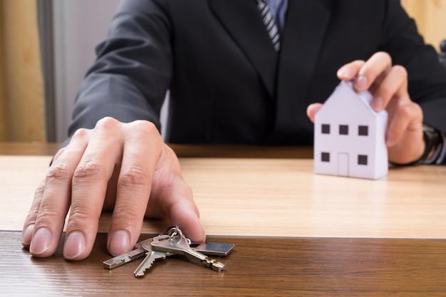 Makelaar met huismodel en sleutels