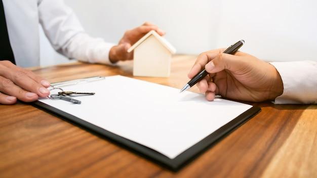 Makelaar met klant die contract ondertekening maakt koop / huur een huis