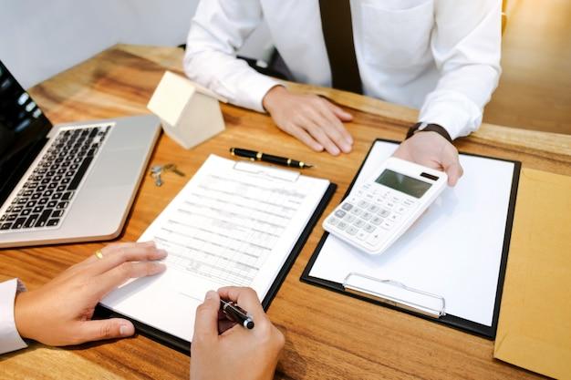 Makelaar met klant die contractondertekening maakt en analyseert waardering