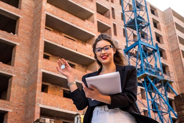 Makelaar sleutel tegen nieuw huis als achtergrond ingedrukt. verkoop concept